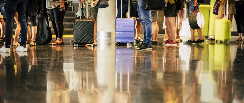 group of people waiting at their flight at the airport - travel concept with passengers waiting to enter at the gate or check-in with their baggage -unrecognizable and mirrored on the floor