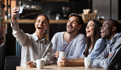 Cheerful diverse millennial friends taking selfie on smartphone in cafe