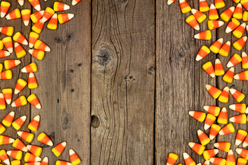Halloween candy corn double side border. Top view on a rustic wood background with copy space.