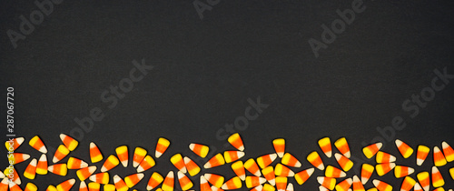 Halloween candy corn bottom border banner. Top view on a black background with copy space.