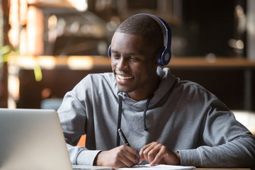 Smiling african young man student wearing headphones study online