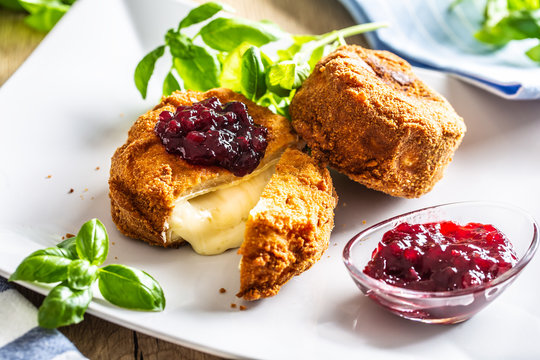 Fried camembert or brie cheese with cranberry jam and basil