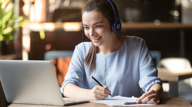 Smiling girl wear wireless headphone study online with skype teacher