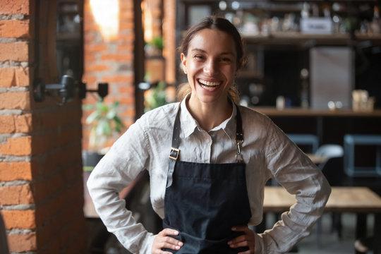 Cheerful young waitress wearing apron laughing looking at camera