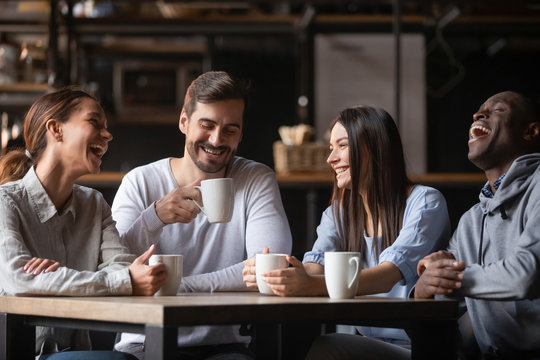 Happy multiracial friends group chatting laughing drink tea in cafe