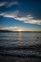 Short waves crash on Lakeside Beach at Lake Tahoe during sunset with mountains splitting the middle of the picture