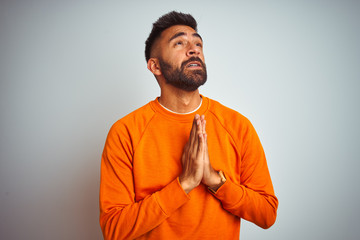 Young indian man wearing orange sweater over isolated white background begging and praying with...