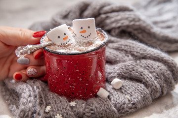 Fotobehang Chocolade Red mug with hot chocolate with melted marshmallow snowman in a woman hands