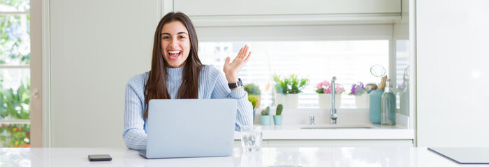 Wide angle picture of beautiful young woman working or studying using laptop very happy and excited, winner expression celebrating victory screaming with big smile and raised hands