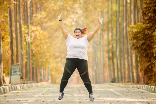 Happy overweight woman jumps at autumn time