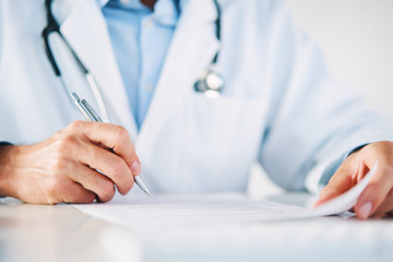Close up of doctor reading and signing files and paperwork of patient