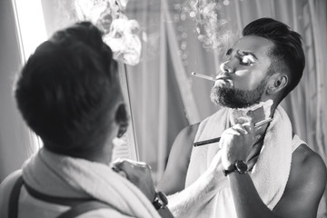 Man looking in the mirror, smoking a cigarette and shaving his beard with a straight razor