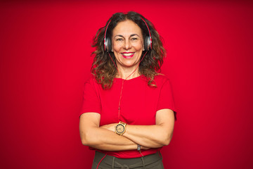Middle age senior woman wearing headphones listening to music over red isolated background happy face smiling with crossed arms looking at the camera. Positive person.