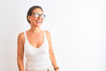 Wall Mural - Middle age woman wearing casual t-shirt and glasses standing over isolated white background looking away to side with smile on face, natural expression. Laughing confident.