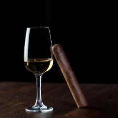 Picture of a Cuban cigar relied on on a glass of white wine,on the wooden table,luxury and well being life concept