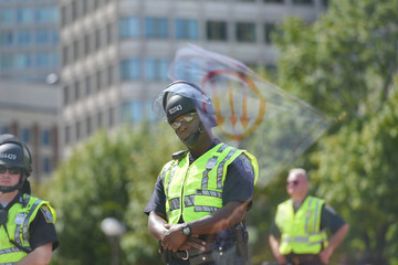 Flag, bearing a leftist symbol associated with Antifa, is reflected behind a Boston Police officer during the Straight Pride Parade rally in Boston