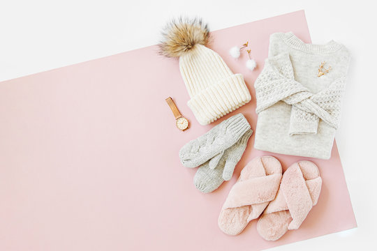 Gray warm knitted sweater with winter hat, mittens and fluffy fur slippers on pale pink background. Women's stylish winter clothes. Flat lay, top view.