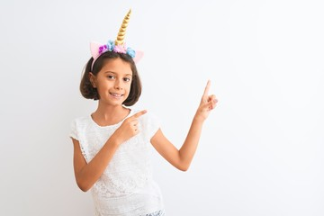 Beautiful child girl wearing unicorn diadem standing over isolated white background smiling and...