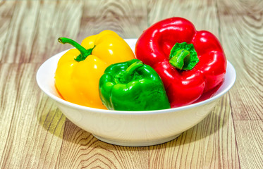 Red, green & yellow bell peppers (capsicum) in a white bowl on a wooden table.
