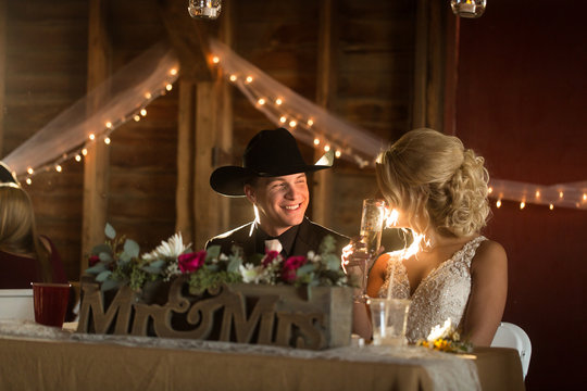 Country bride and groom sitting at reception
