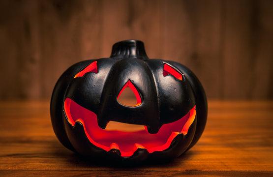 Black halowwen pumpkin on wooden background / Haloween background concept with jack-o-lantern