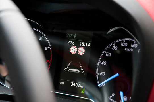 Modern car dashboard with speed limit and overtaking signs