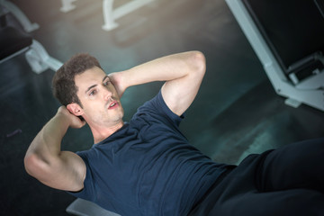 Handsome man exercising doing sit up abdominal exercise in gym