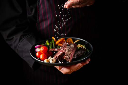 Grilled and sliced beef steak with grilled vegetables served on black plate on black background presentation in chef hands