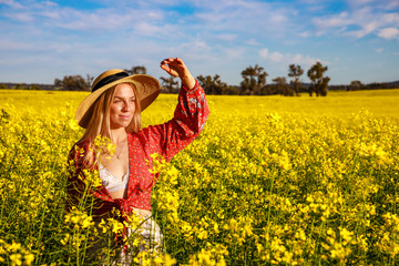 Happy young lady with straw hat in yellow Canola Field in Western Australia