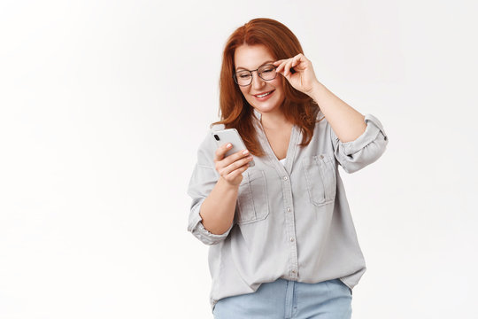 Let look what we got. Gorgeous elegant modern redhead middle-aged mom wear glasses read message check out son send photos social media look smartphone display smiling delighted, white background
