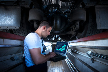 Vehicle mechanic with diagnostic tool laptop working under the truck in workshop. Experienced worker reading parameters and detecting problem. Car or truck service and maintenance.