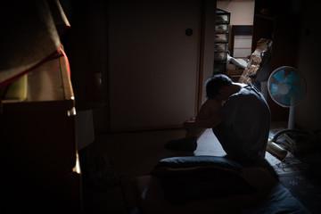 ひきこもり男性のイメージ写真。社会問題のイメージ。