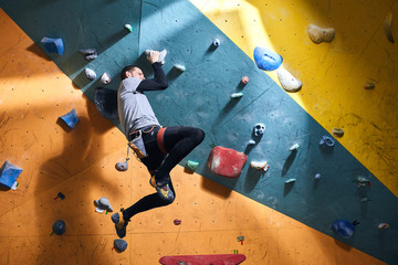 Young athletic sportsman has dynamic training in bouldering gym, runs out of energy, feels tired...