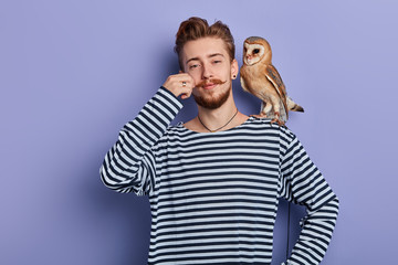 cheerful funny cunning guy in striped sweater taking money from tourist for taking a pictire with an owl, isolated blue background, studio shot, business concept