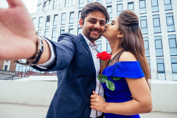 happy asian man in stylish black suit making selfie photo with his beautiful woman after proposal and giving gold ring on the background of the restaurant street downtown business center office