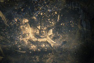 Dark stained abstract background. Rust dust. Golden smeared powder on black surface.