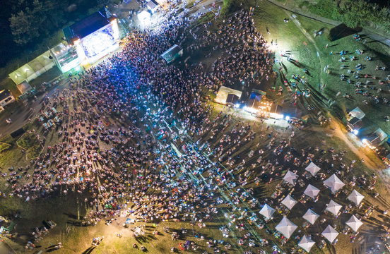 Top view of crowd people by the stage at outdoor concert of pop singer. Night scene.