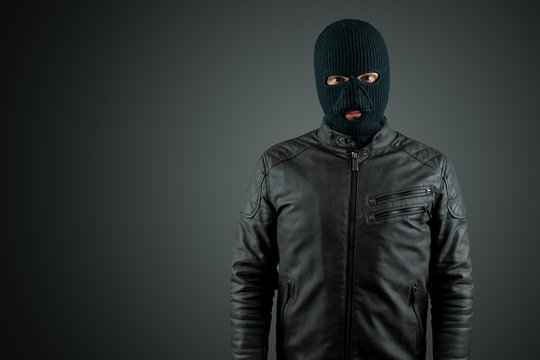 Robber, thug in a balaclava on a black background. Robbery, hacker, crime, theft. Copy space.