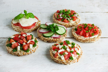 rice crisp cracker with chopped vegetables tomato cucumber radish parsley soft cheese on white wooden table