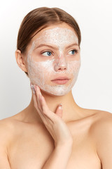 serious attractive girl has applyed scrub mask on face. close up portrait, girl with a plam on her cheek looking aside