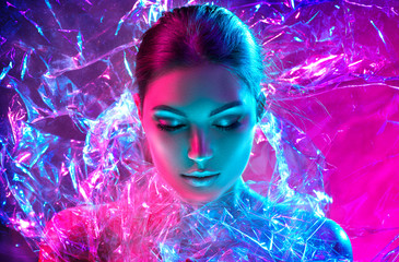 Papiers peints Beauty Fashion model woman in colorful bright neon lights posing in studio through transparent film. Portrait of beautiful sexy girl in UV. Art design colorful makeup