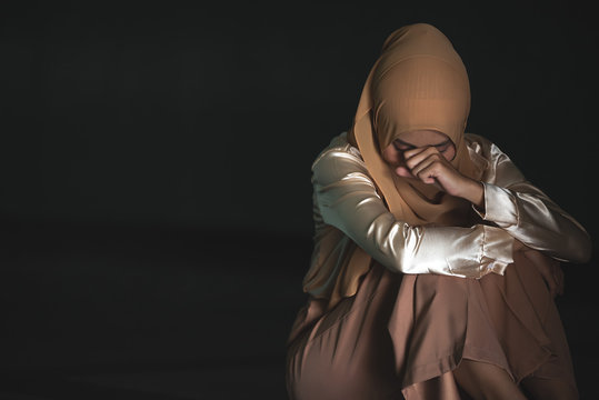 Young Muslim women sitting and feeling pain.. Lonely Muslim girl harly thinking how to solve life problem.