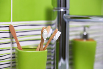 Bamboo toothbrushes in green glass in bathroom