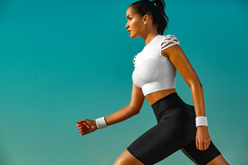 Sporty young woman and fit athlete runner running on the sky background. The concept of a healthy...