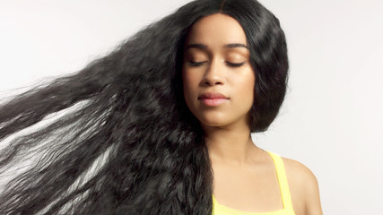 beauty mixed race african american model in studio portraits with long hair wig natural makeup watching aside with hair blowing