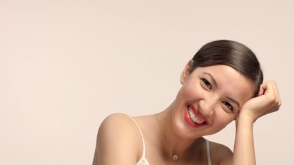 beauty brunette with short haircut model in studio alone with ideal shiny skin laughing in studio. Pink tonality