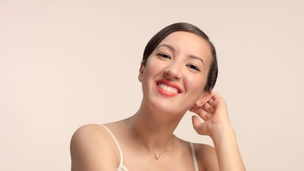 beauty brunette with short haircut model in studio alone with ideal shiny skin happy smiling