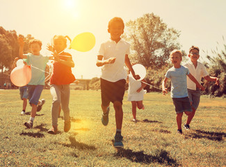 Group of kids with balloons running in race and laughing in park Wall mural