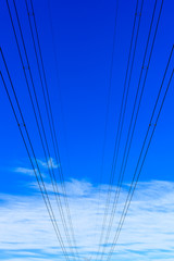 Electricity powerlines against a blue sky with light white clouds