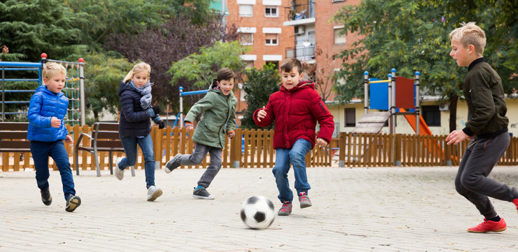 Group of laughing children playing football